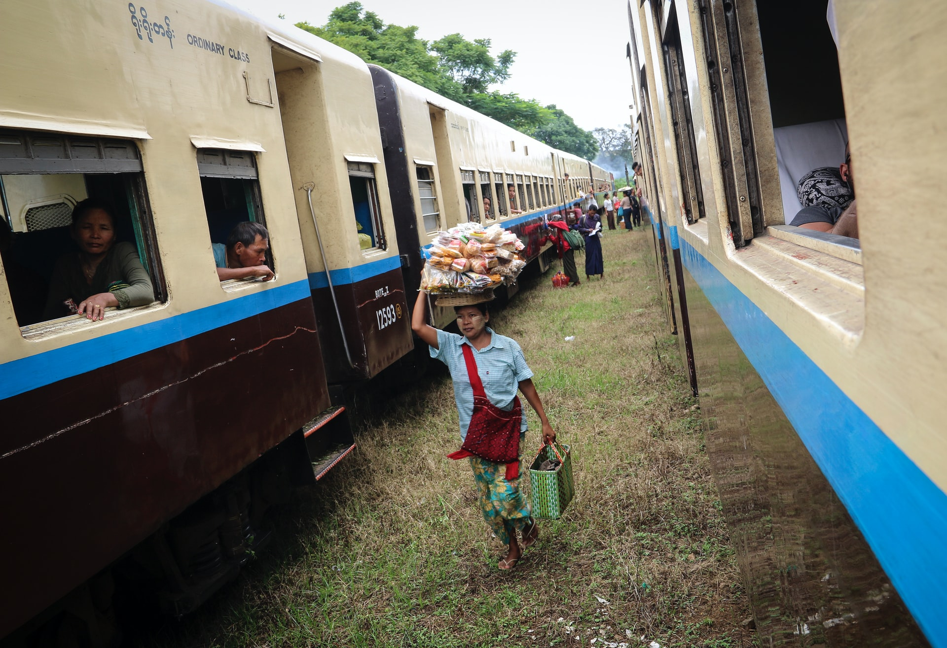 A snack lady selling street food to passengers on a train in Myanmar