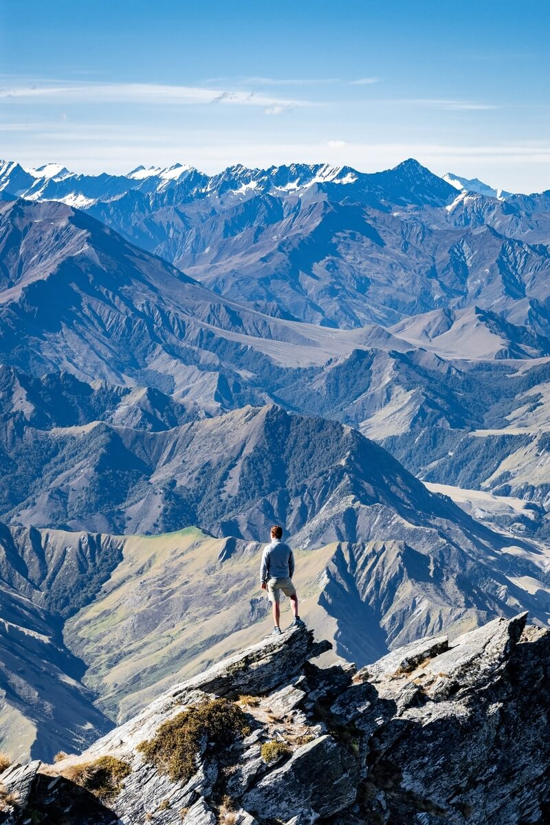 A backpacker hiking in the Queenstown area at the viewpoint on the Ben Lomond trail