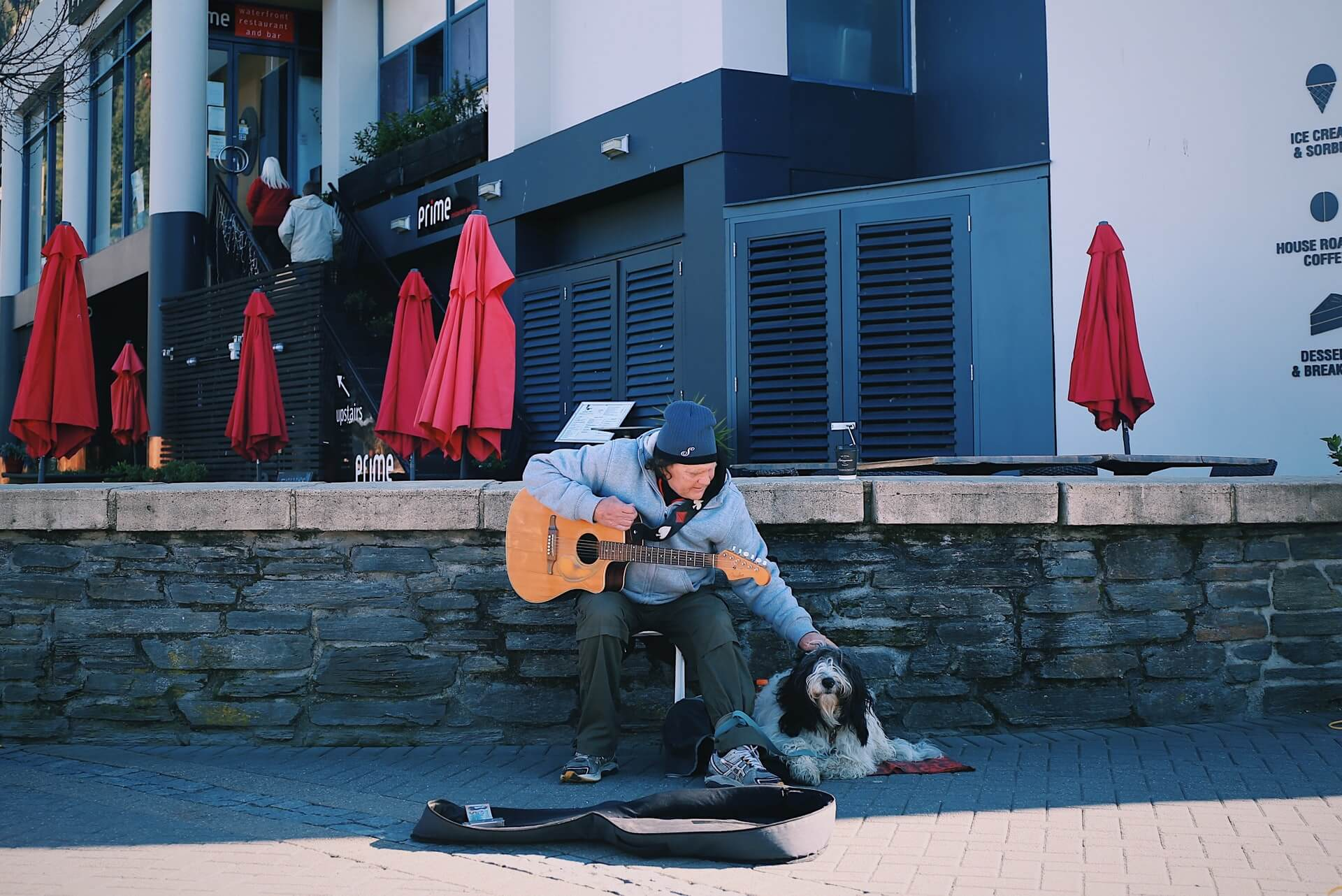 A busker at the Queenstown lakefront market pats his dog