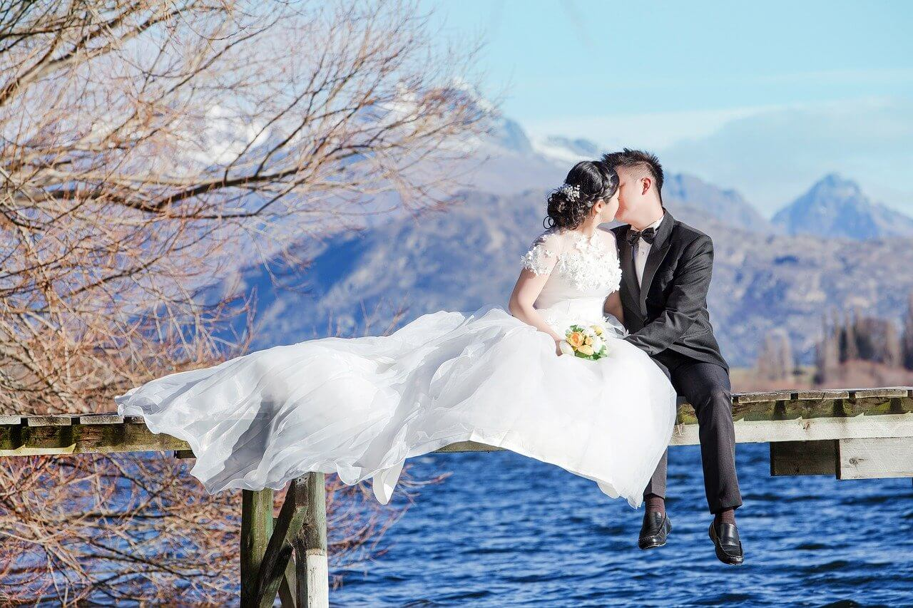 A newly married couple pose for a photoshoot in front of Queenstown's waterfront