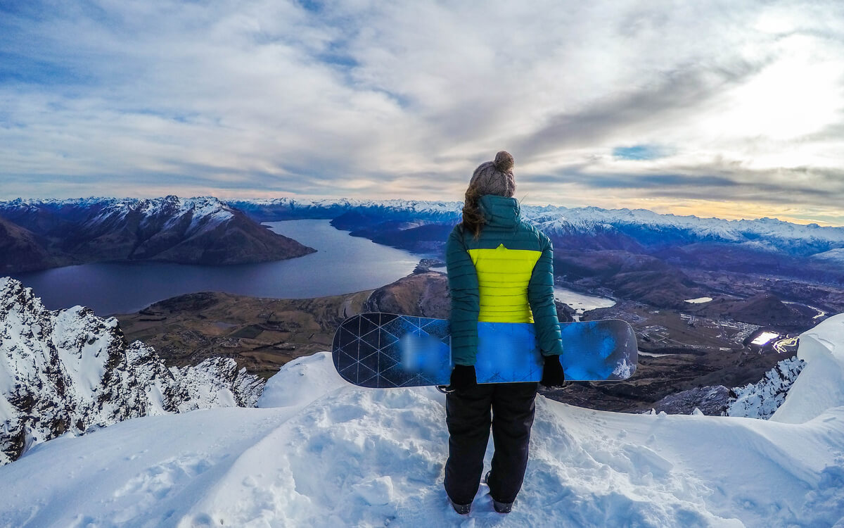 A snowboarder in Queenstown at a lookout in the Remarkables overlooking Lake Wakatipu