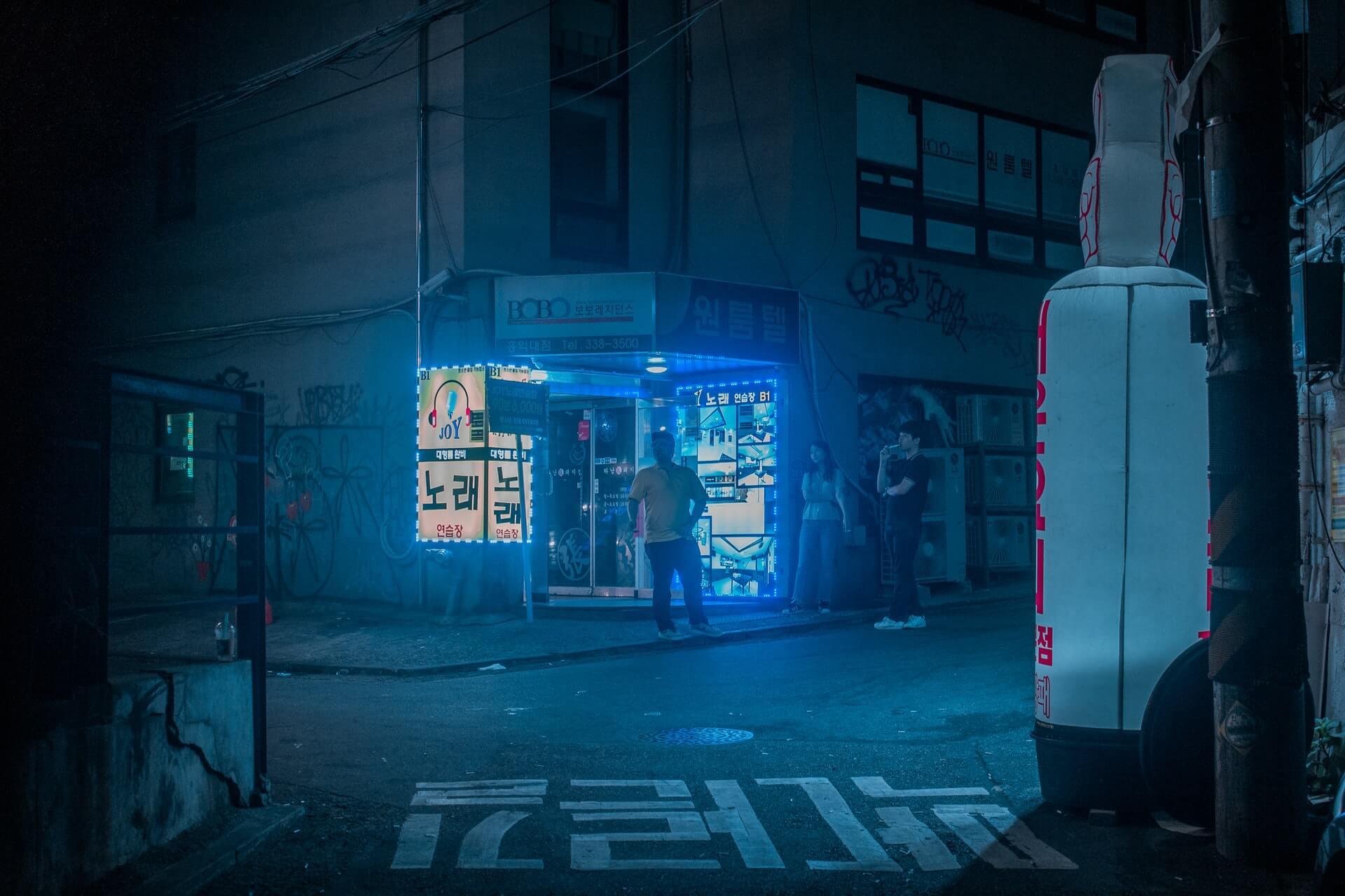 A blue-lit neon street featuring Seoul's underground nightlife
