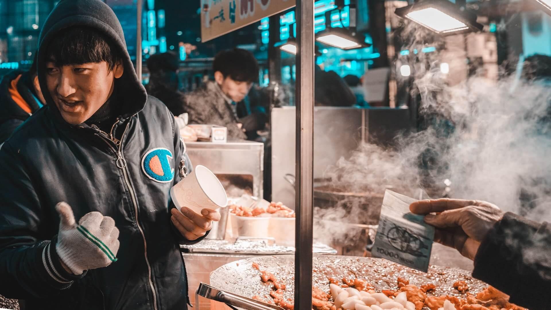 A Korean man serving up street food in Seoul