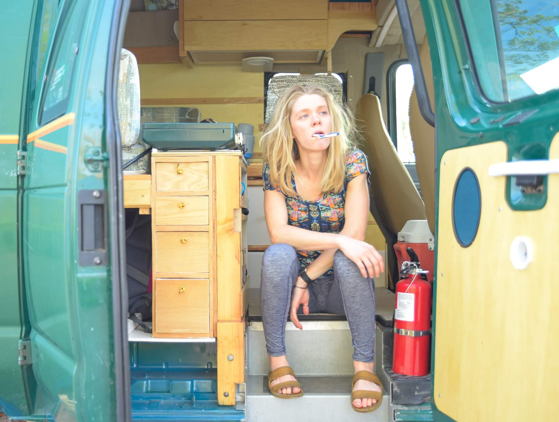 A woman brushes here teeth in a neatly packed motorhome