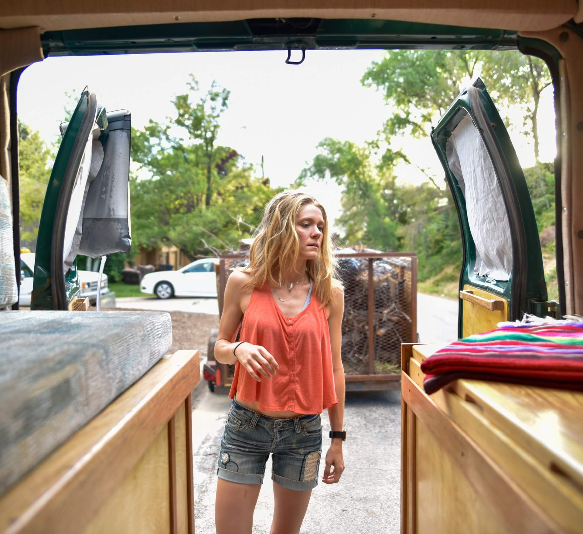 A woman contemplates her RV packing list while organising from the back doors