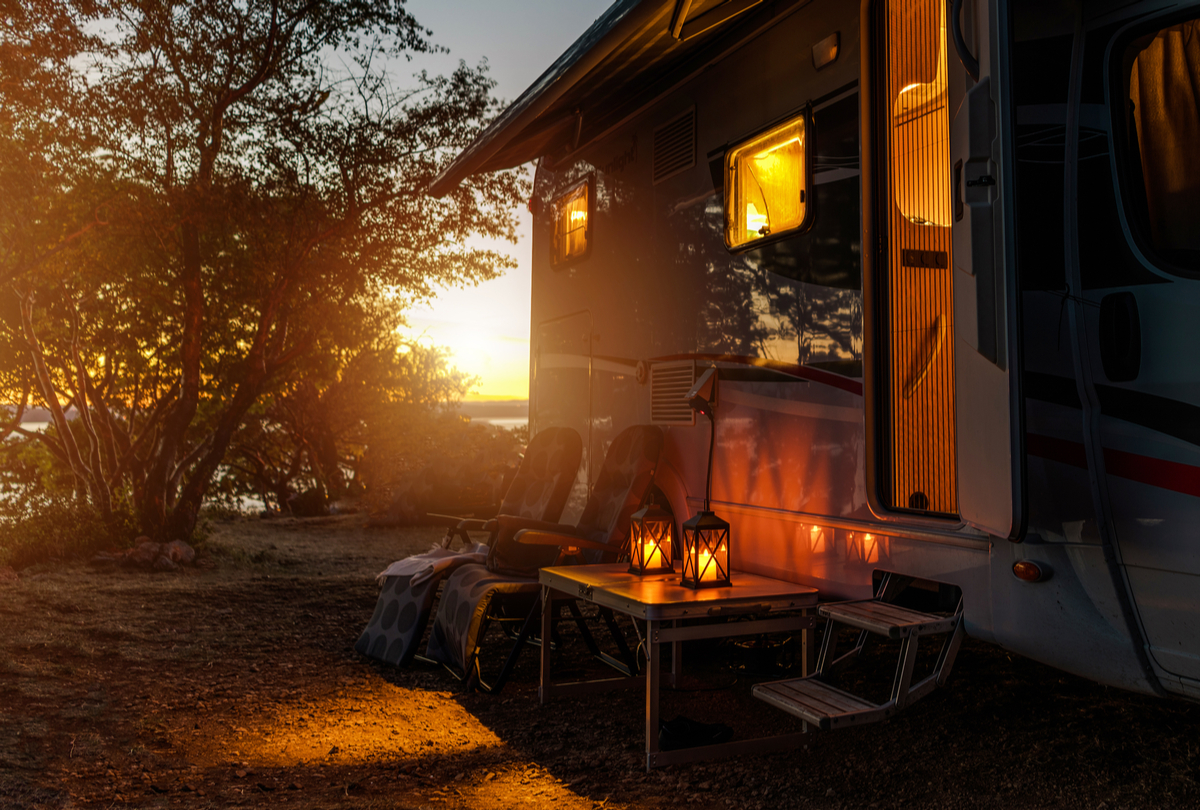 An RV camped at sunset with a perfectly packed setup of supplies and equipment