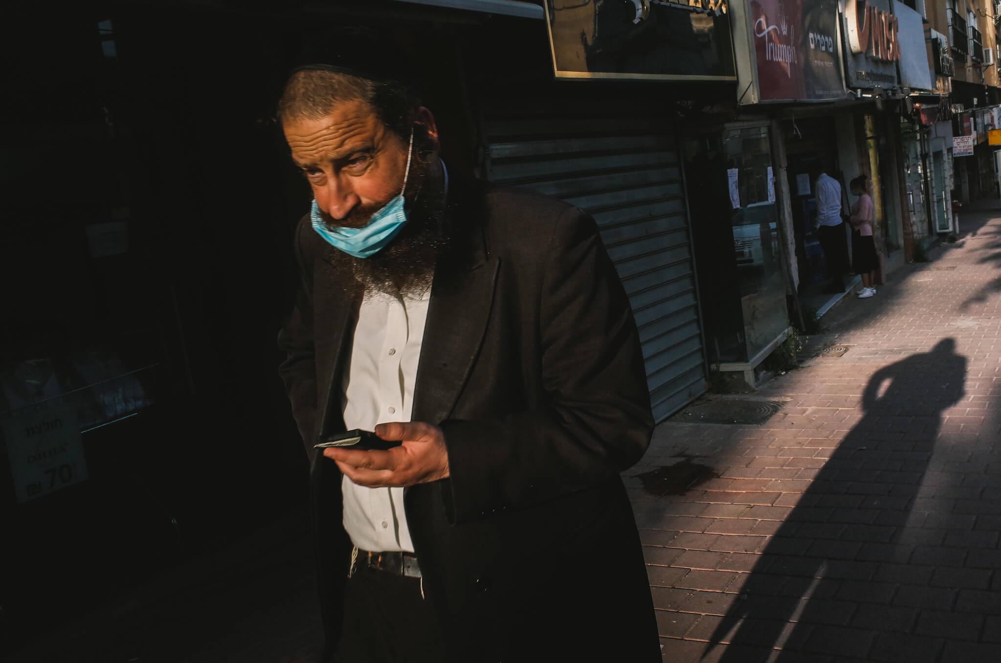 An Ultra-OrthodoxJew in Jerusalem wears a mask per COVID restrictions in Israel