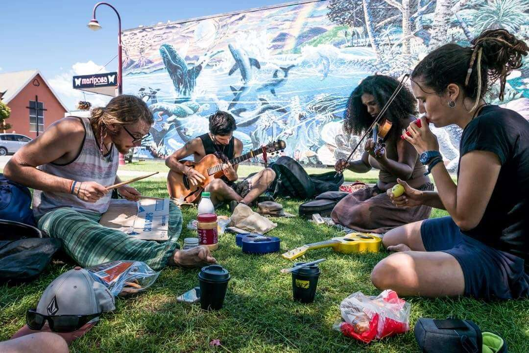 A group of hippy travellers jamming in the park - another reason to travel again in 2021