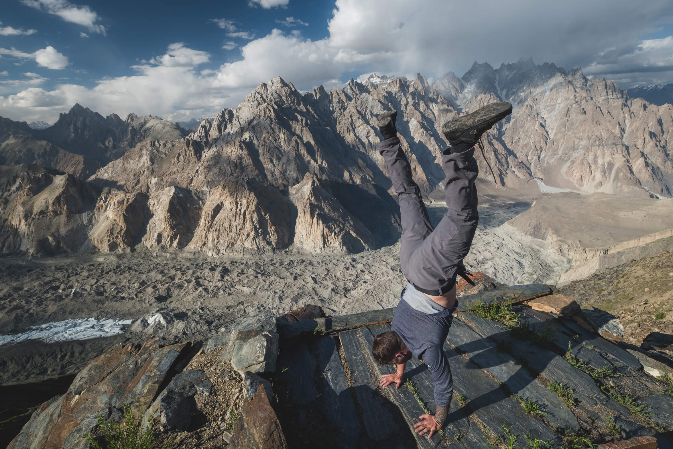 Will Hatton doing a handstand over the Passu Cones in northern Pakistan