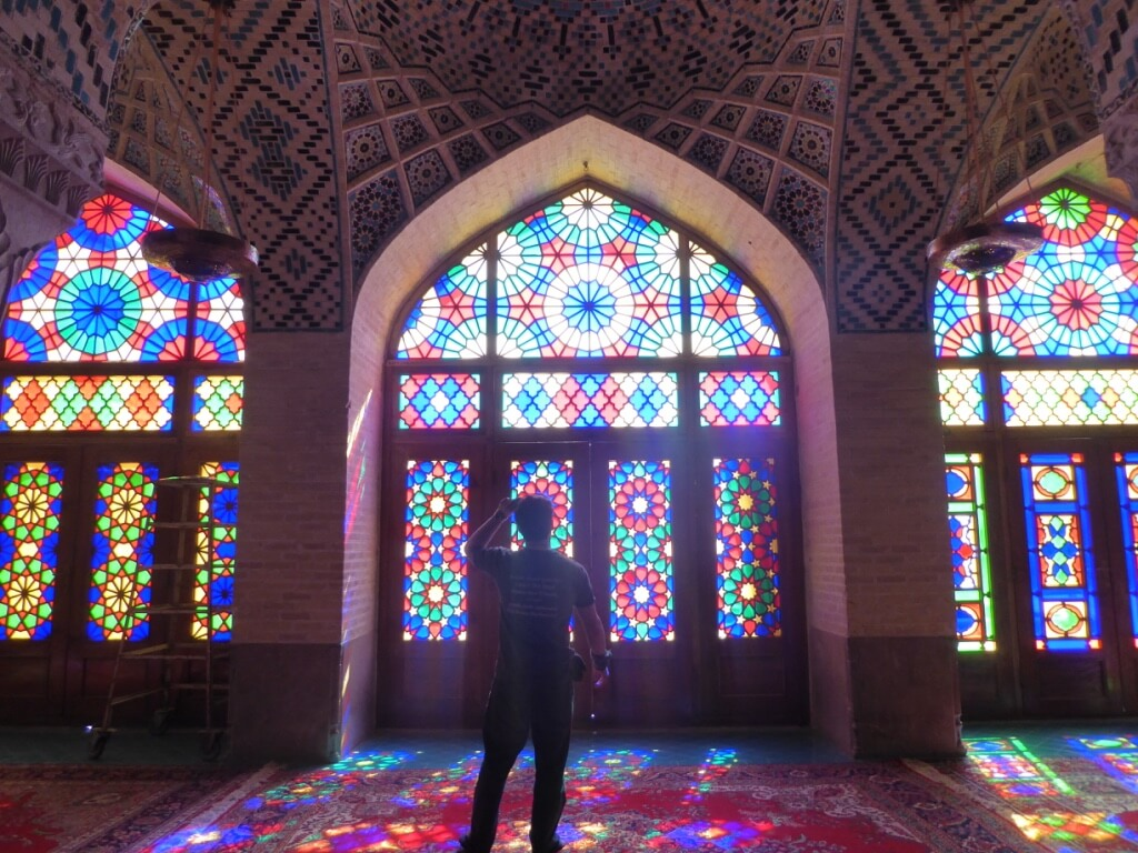 Will Hatton in awe in front of a stained glass window in a mosque while budget backpacking in Iran
