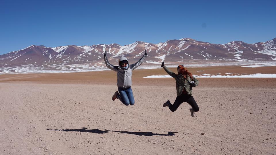two solo female travellers jumping in the air in front of snow capped mountains