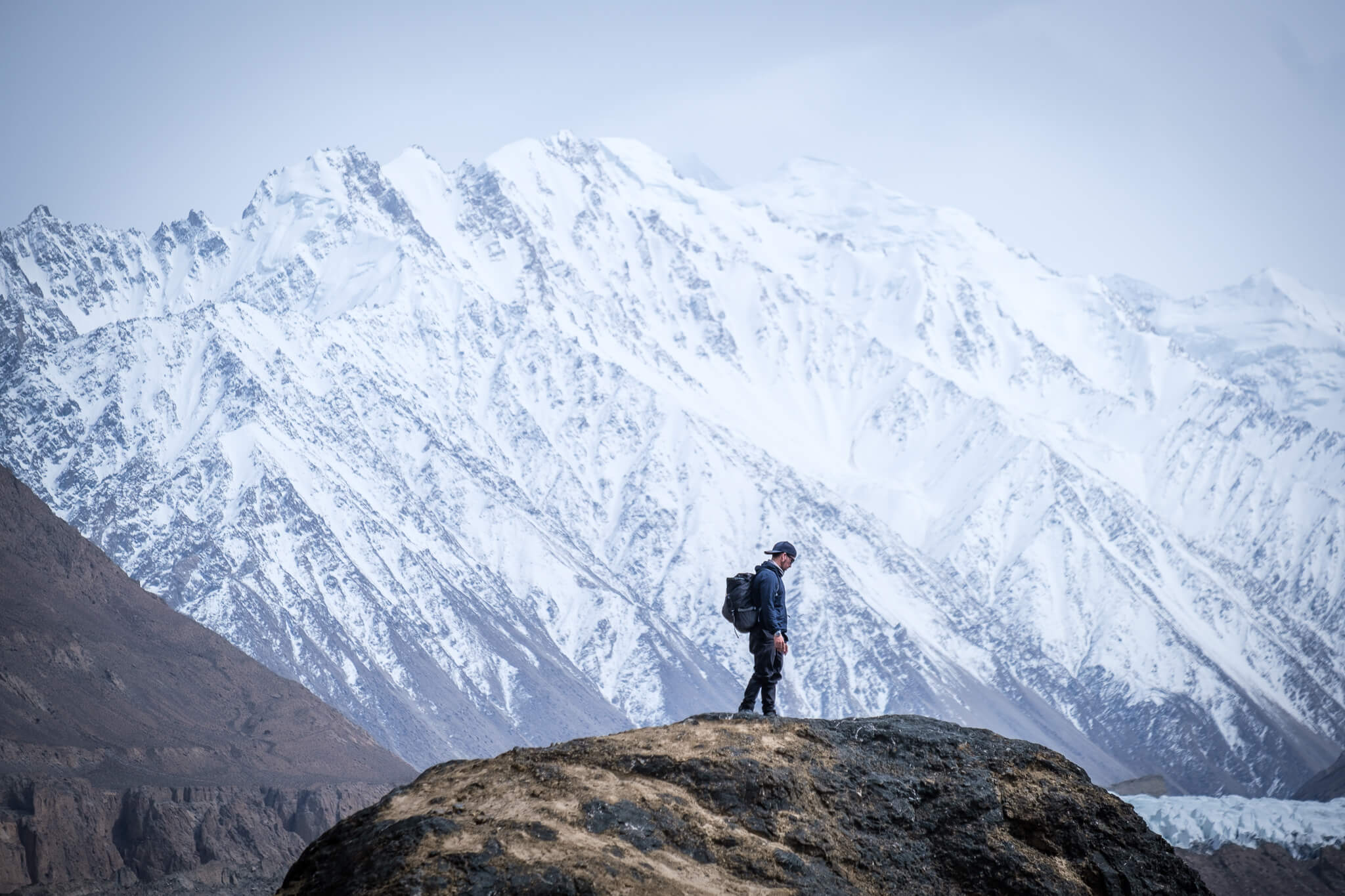 Will standing on a boulder with an icy mountain behind him in Pakistan