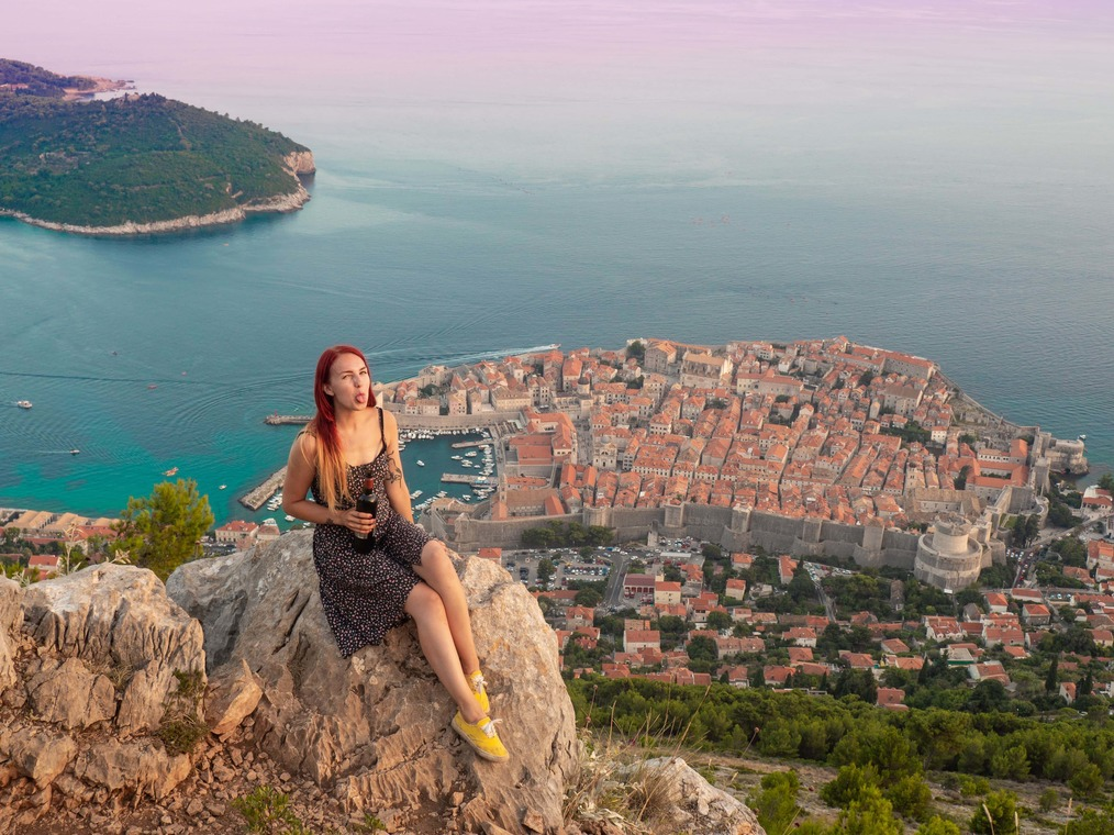 solo female backpacker looking over Dubrovnik, Croatia with a bottle of wine in hand