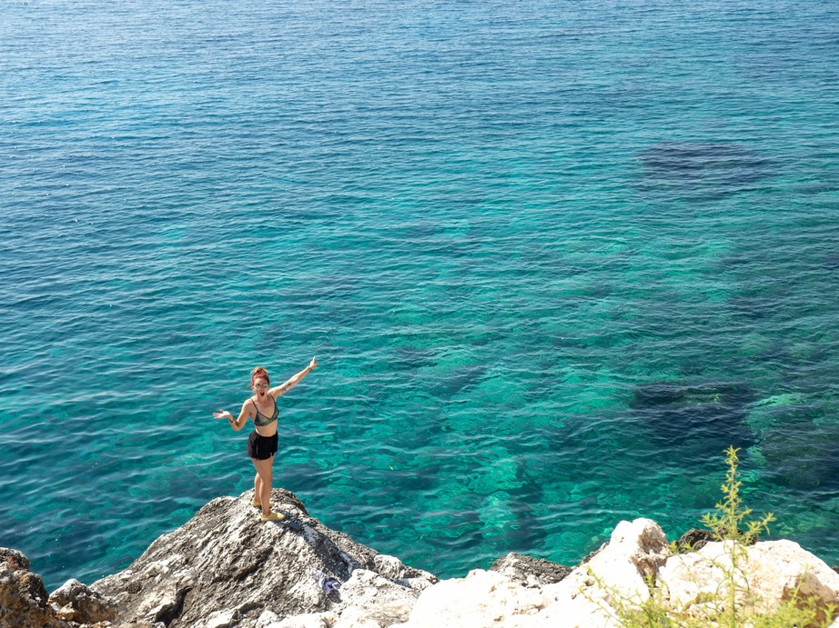 a solo female traveller pointing at a very blue sea