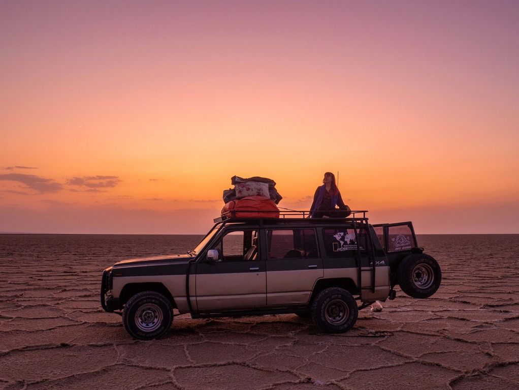 solo female traveller on top of a jeep in front of sunset