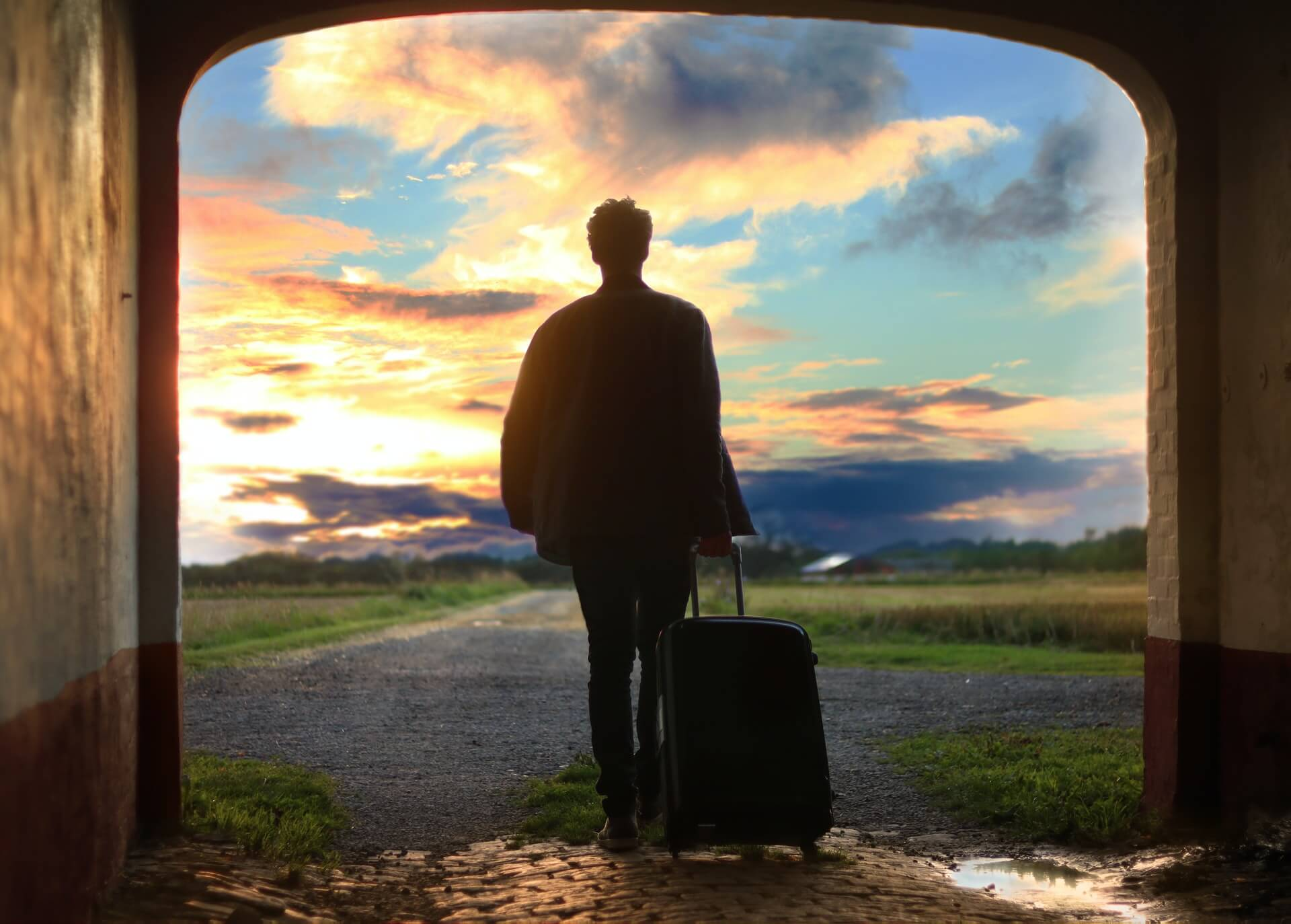 A man travelling without friends or problems exits a tunnel into a sunset