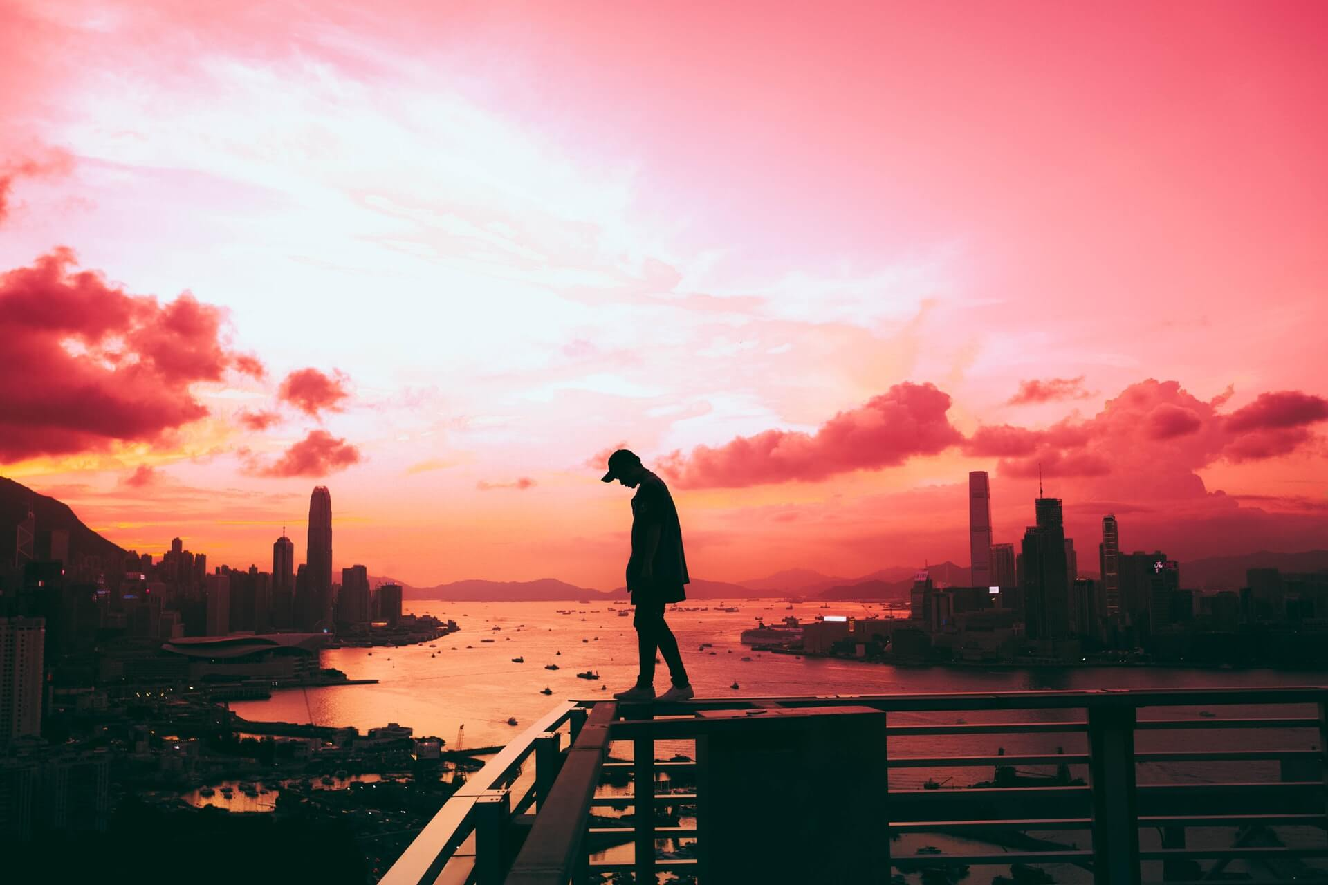 A man silhouetted against a crimson sunset in Hong Kong
