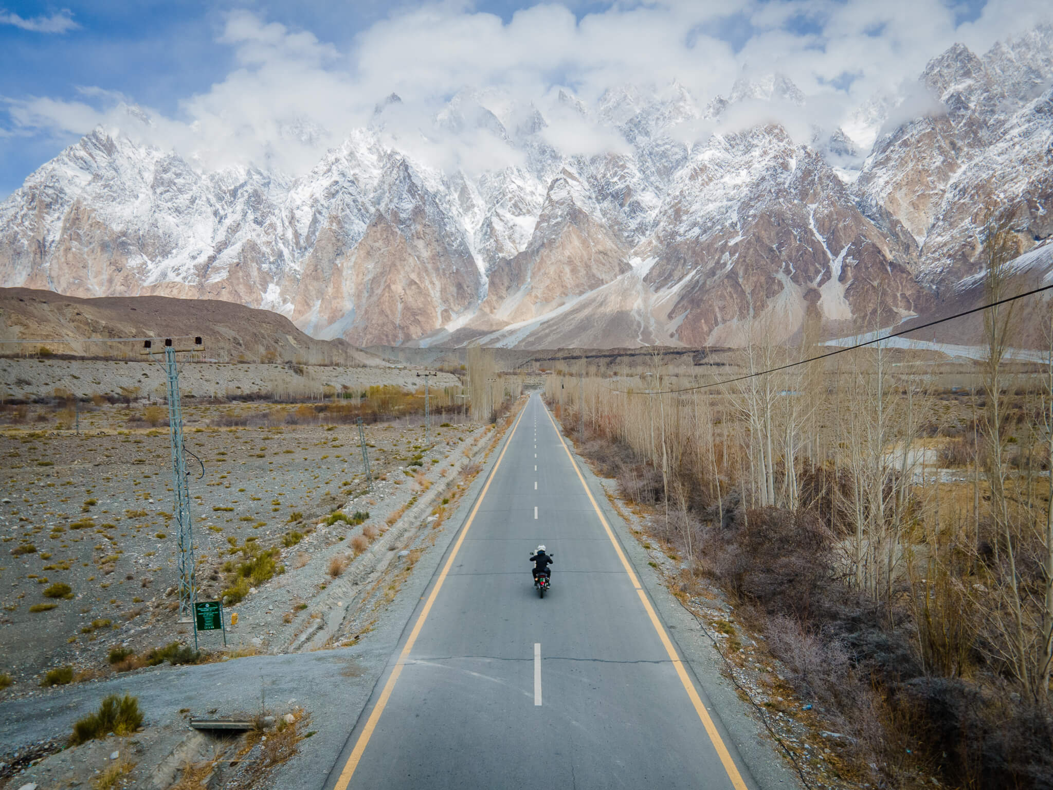 Will riding away from his travel problems down an empty highway in Pakistan
