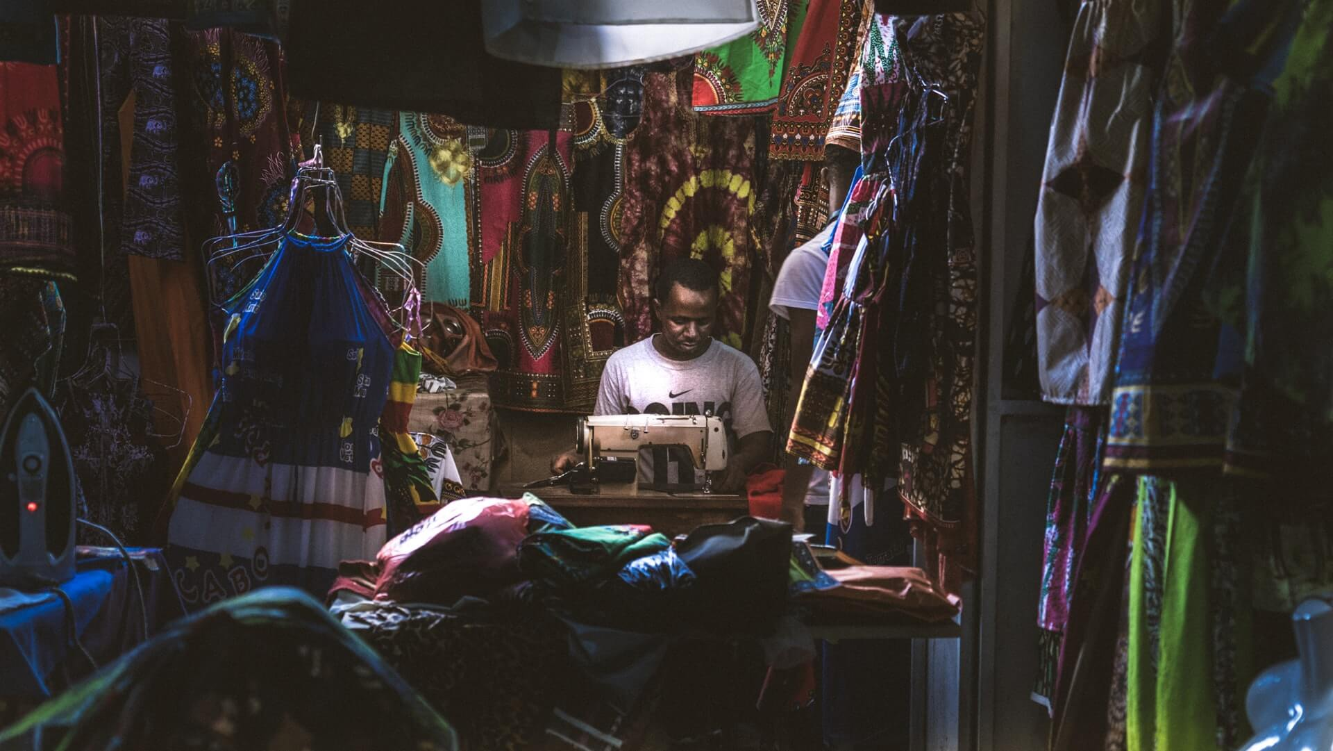 A tailor in his shop in Cape Verde working at a sewing machine