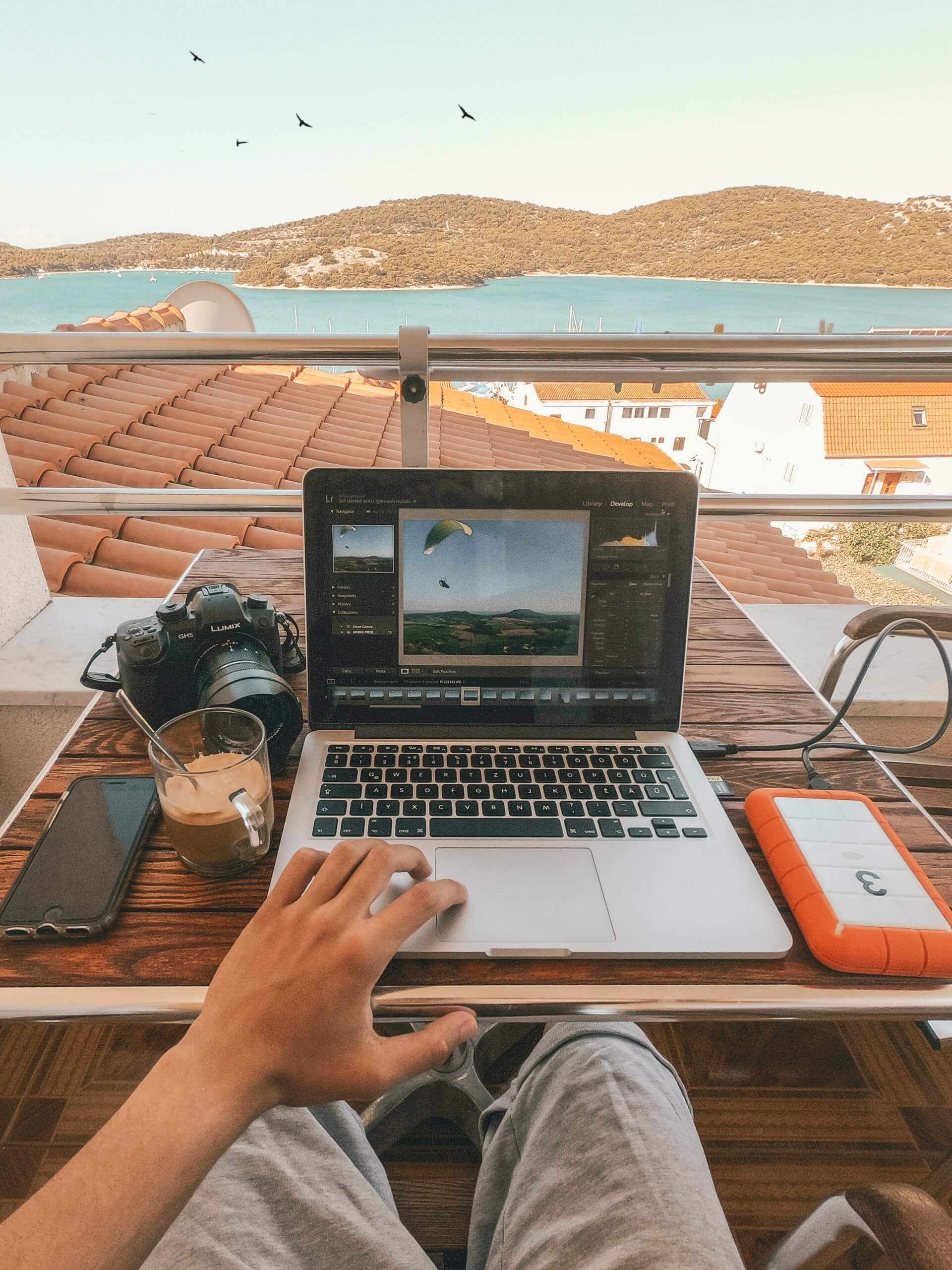 A remote worker in Croatia working at his laptop on a balcony