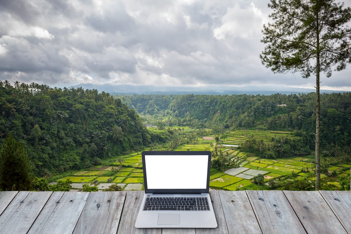 A laptop on a perch over a valley while someone works remotely from another country