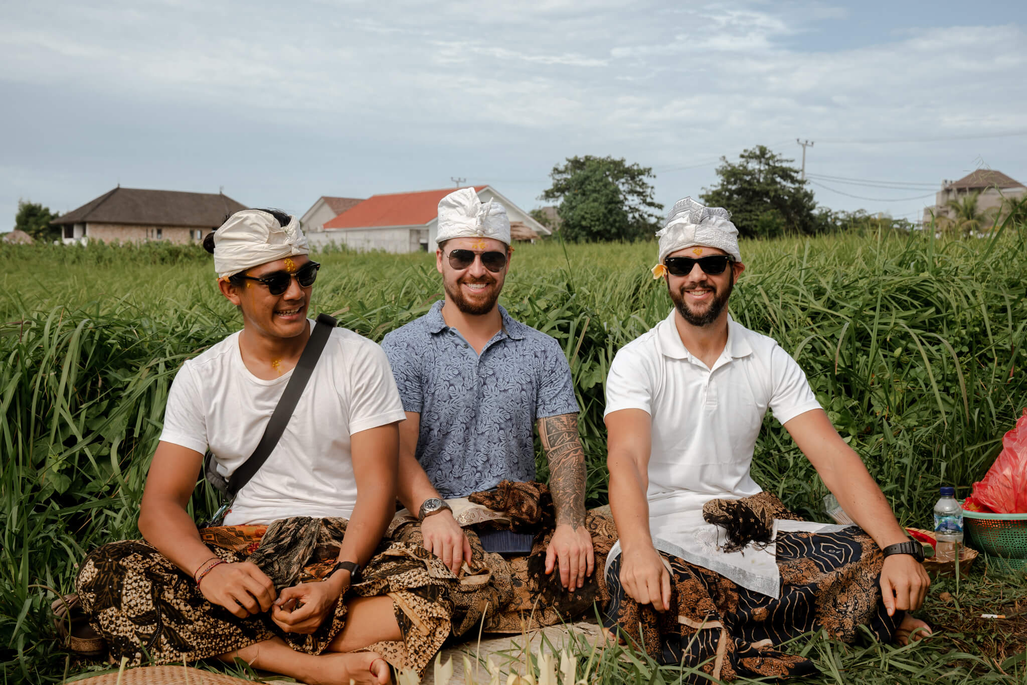Will Hatton and two more men sitting in a rice paddy in Bali in ceremonial garb