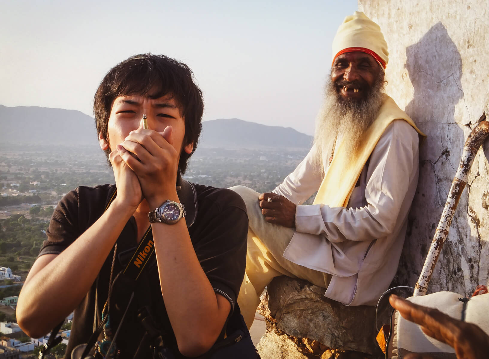 A backpacker travelling India smokes weed with an old local man