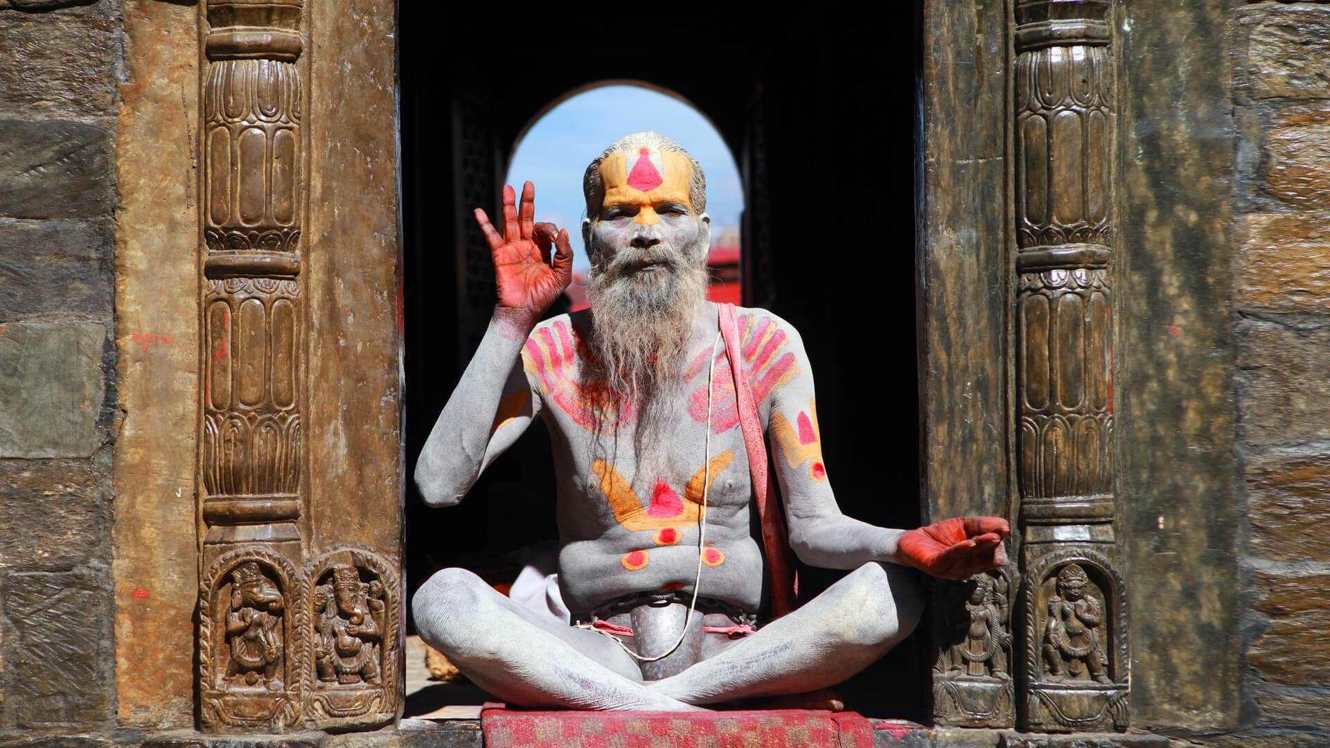 A sadhu in India giving the ok symbol over a well executed drug tourism guide