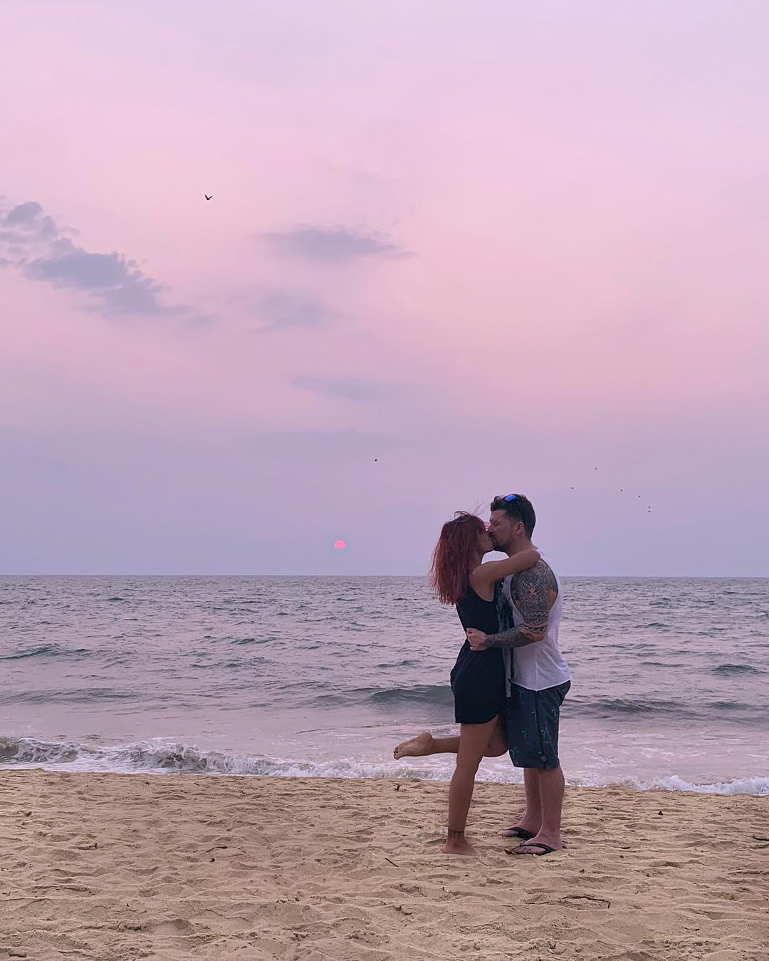 Will and Nina embracing on a beach