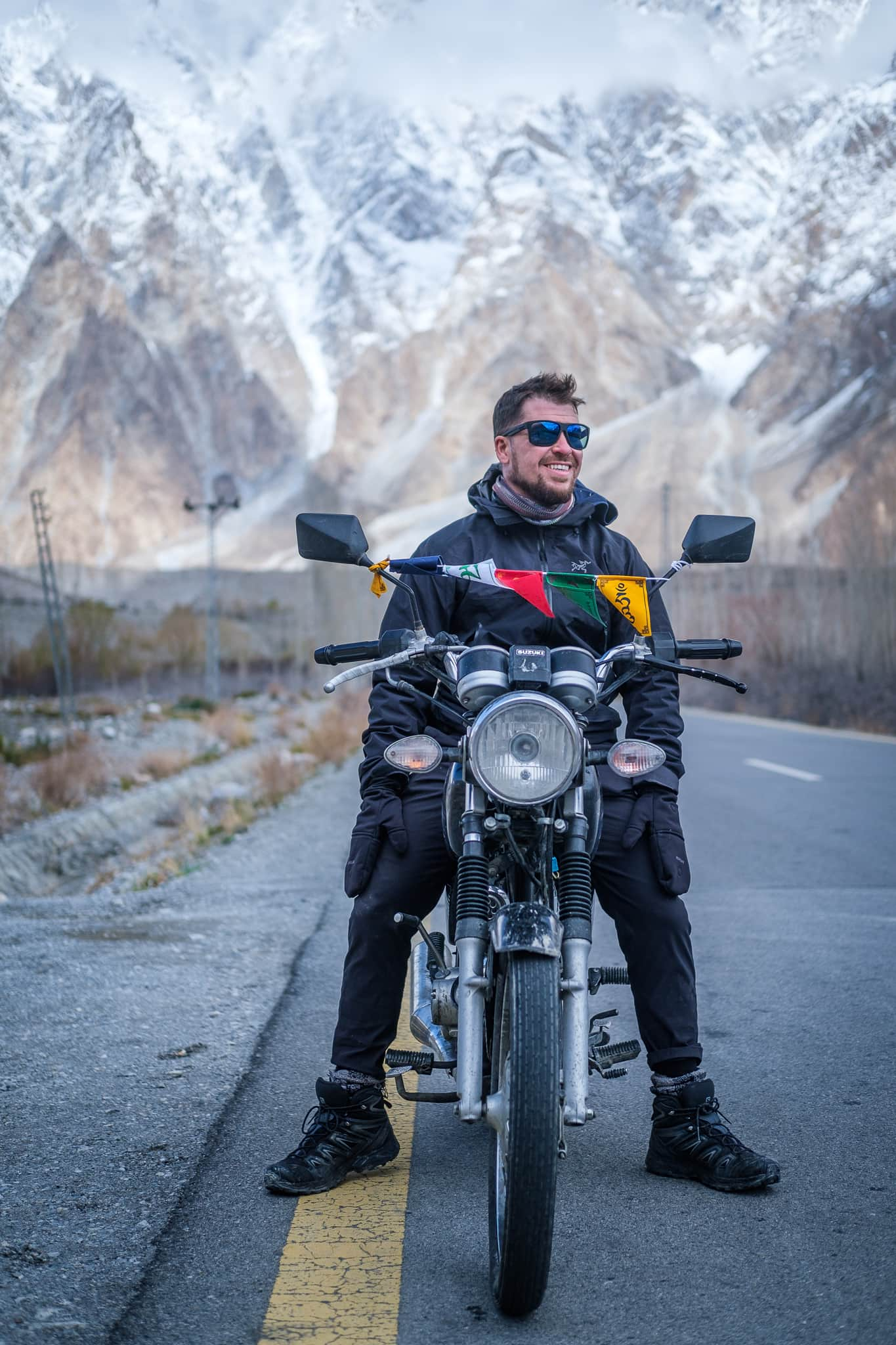 Will on a motorbike with mountains behind him