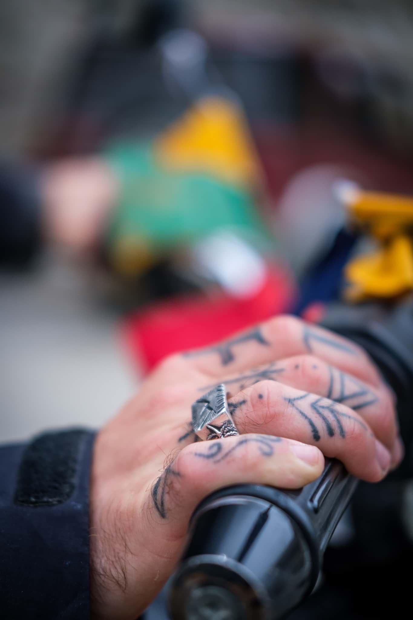 Hand with travel tattoos on a motorbike handlebar