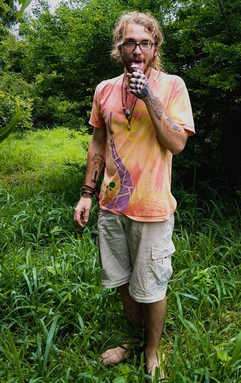 Ziggy standing in a forest eating ice cream showing his travel tattoos