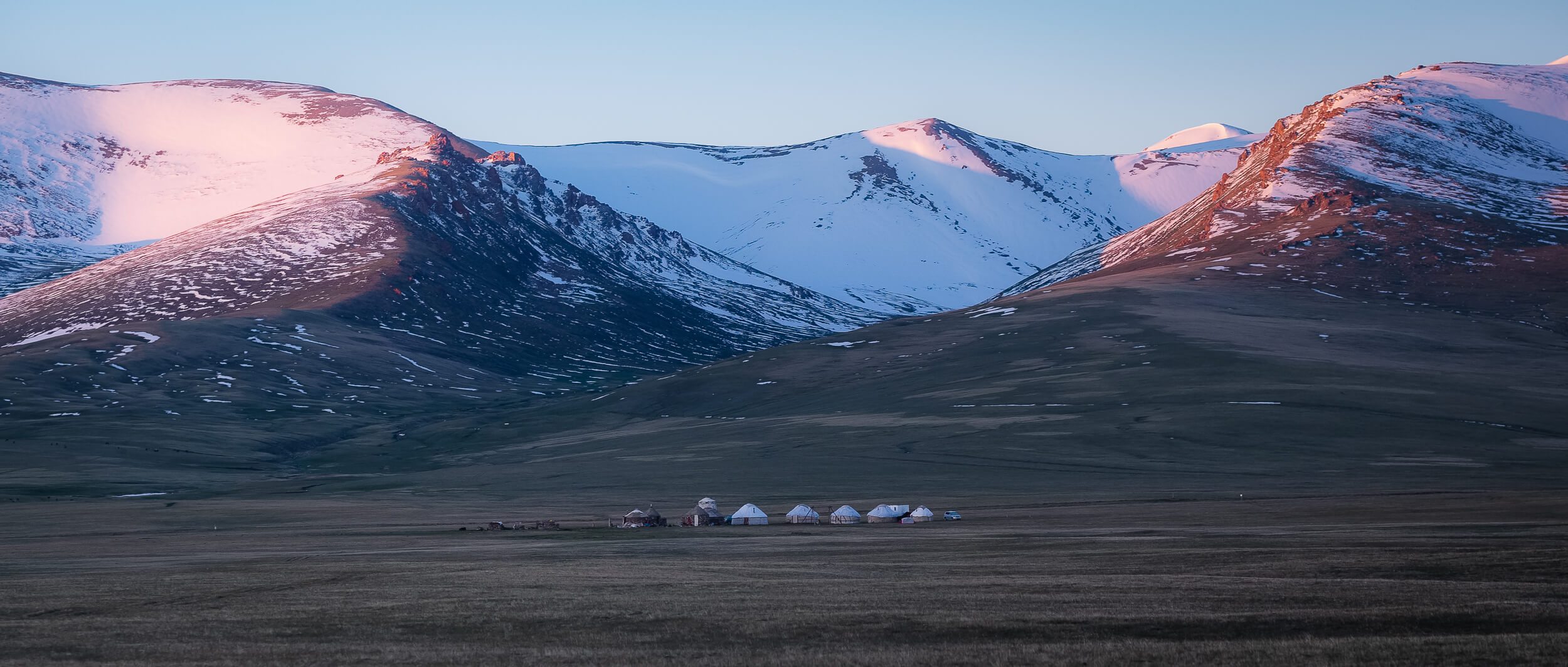 Yurts on a flat backdropped by snowcapped mountains in Kyrgyzstan - - next undiscovered holiday destination