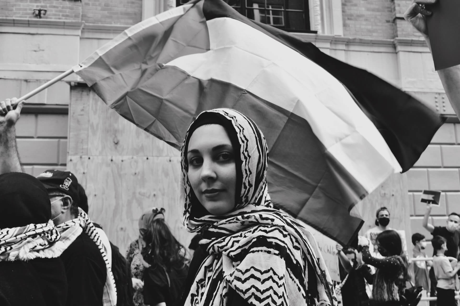 A Palestinian woman with a flag behind her at a protest in Palestine