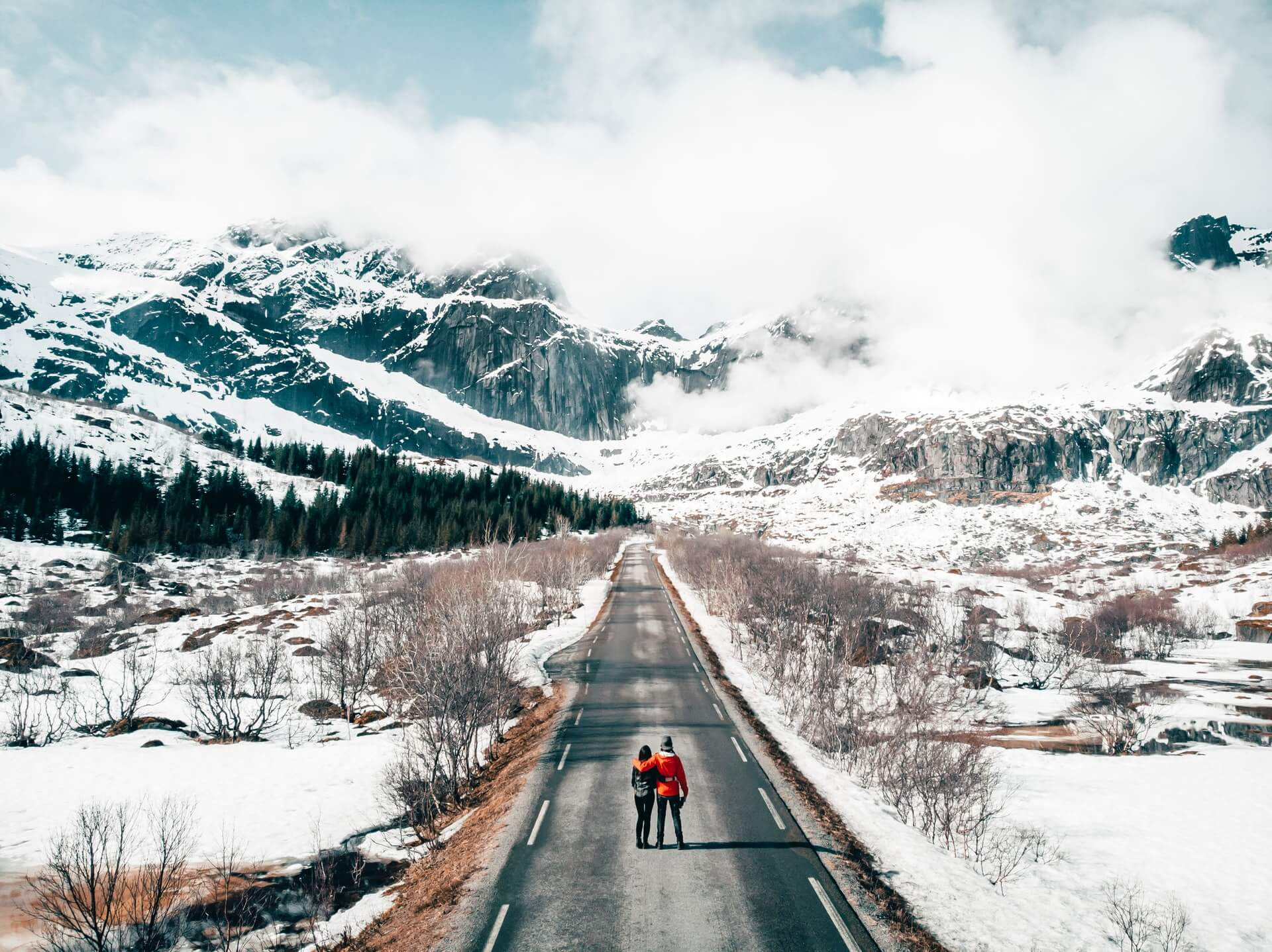 A young travelling couple on a long icy road in Norway seek new undiscovered holiday destinations