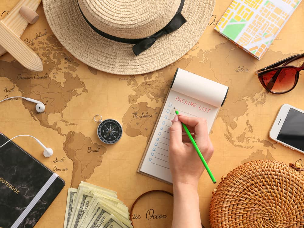 woman writing a travel packing list