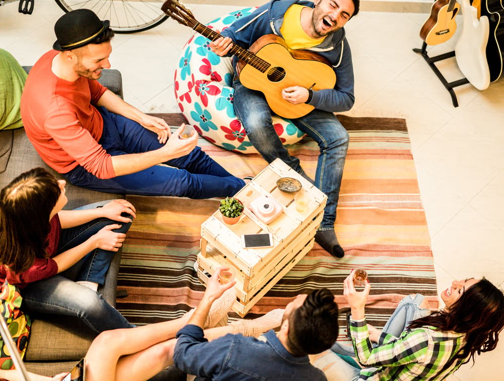Group of backpackers in a hostel common room listening to a guy playing the guitar.