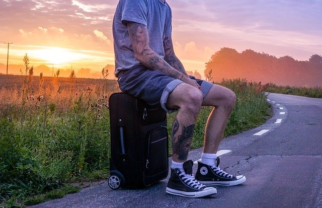 man with travel tattoos sitting on a suitcase by a road with the sunset behind him