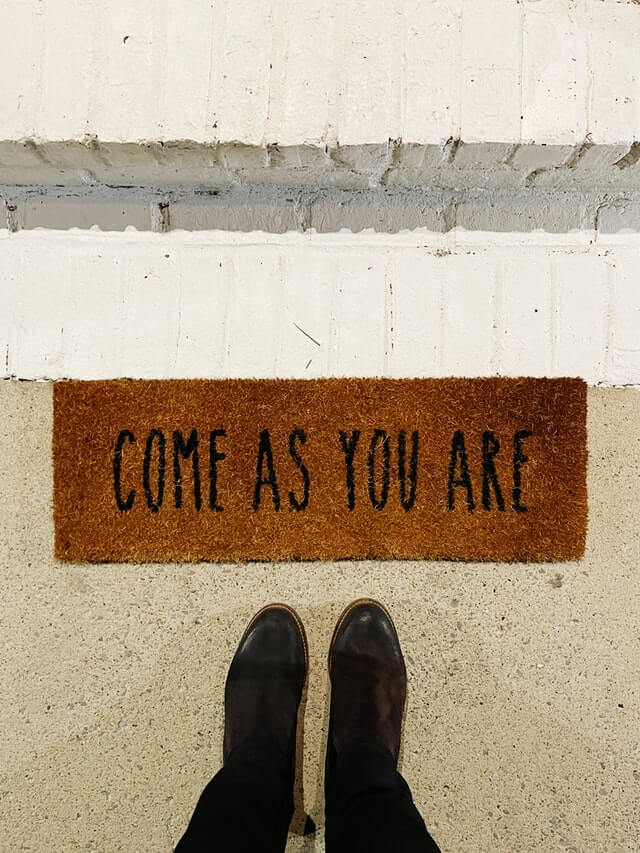 A doormat with the phrase 'Come as You Are' defining hostels in a sentence