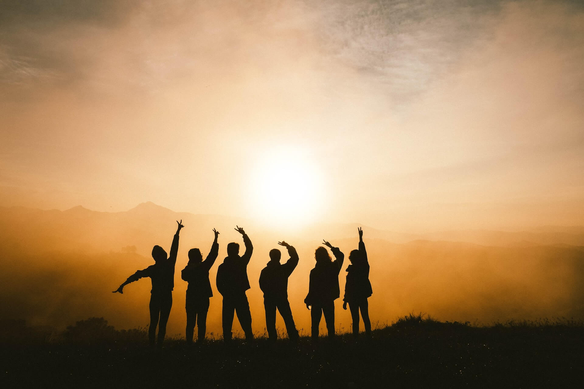 A group of travellers who met while staying in a hostel for the first time silhouetted against a sunset