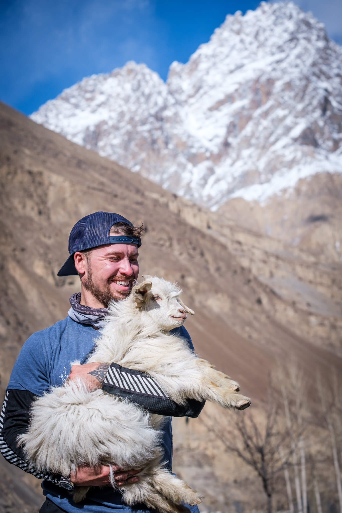 Will Hatton forgetting his travel problems while cuddling a goat in Pakistan