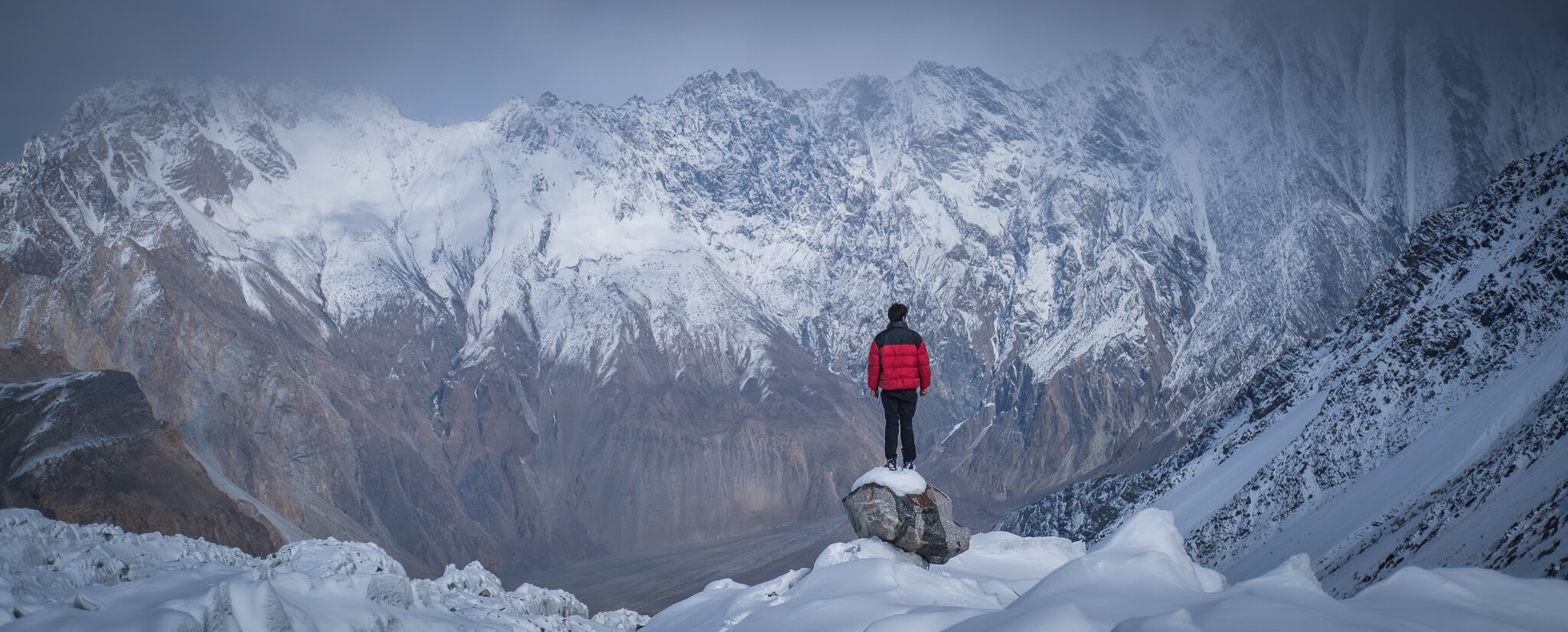 Will stands at en epic lookout in front of a snow-covered mountain in Pakistan