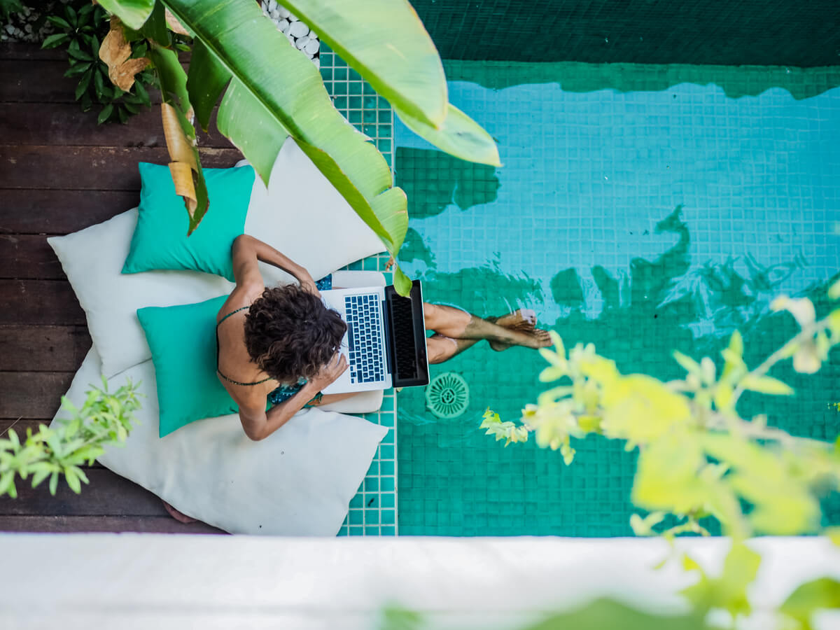 A digital nomad with her essentials working by the pool