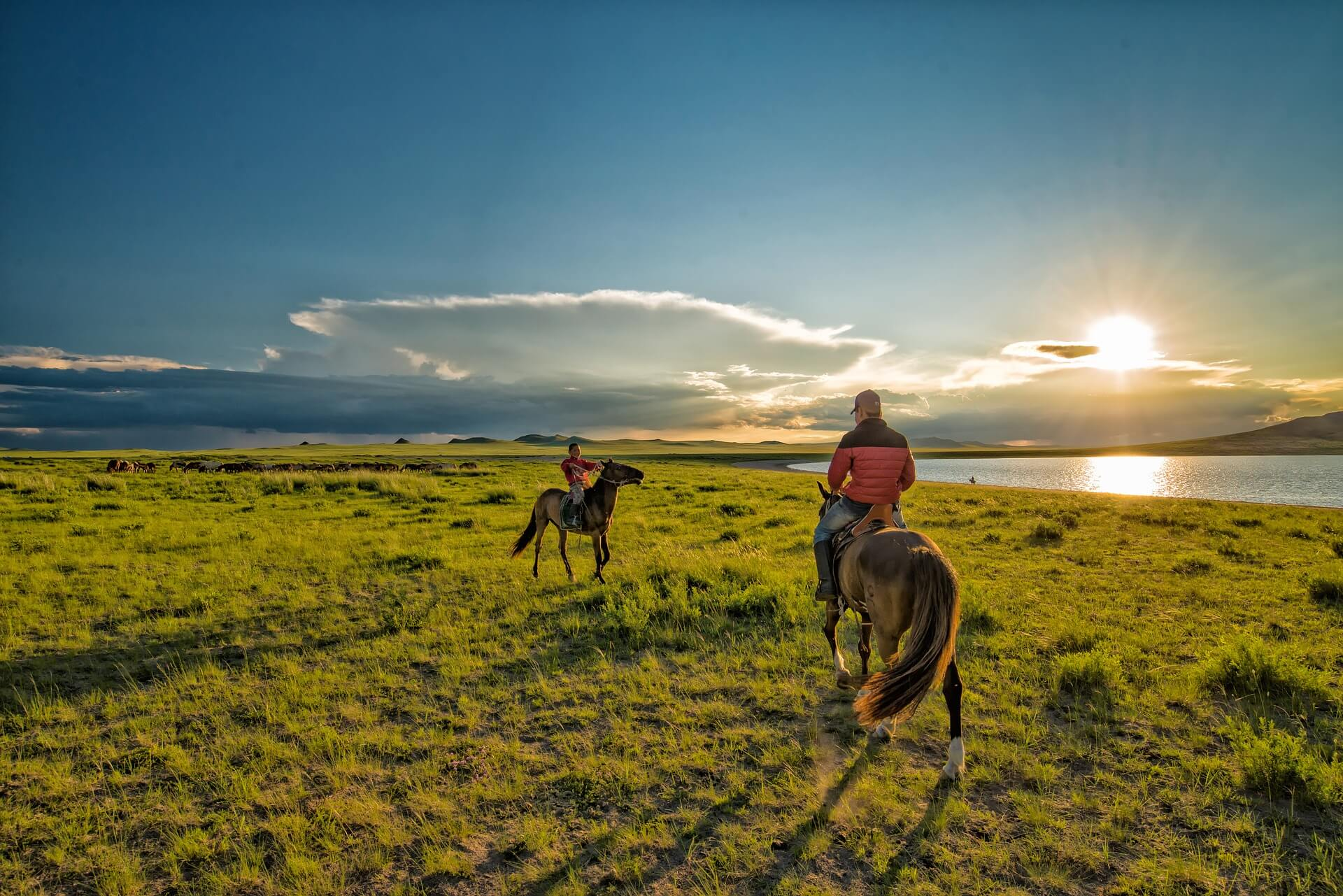 two people riding horses in mongolia