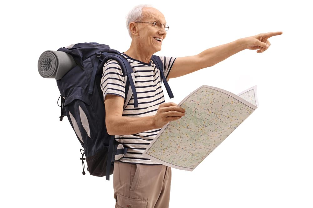 Old backpacker with a map pointing