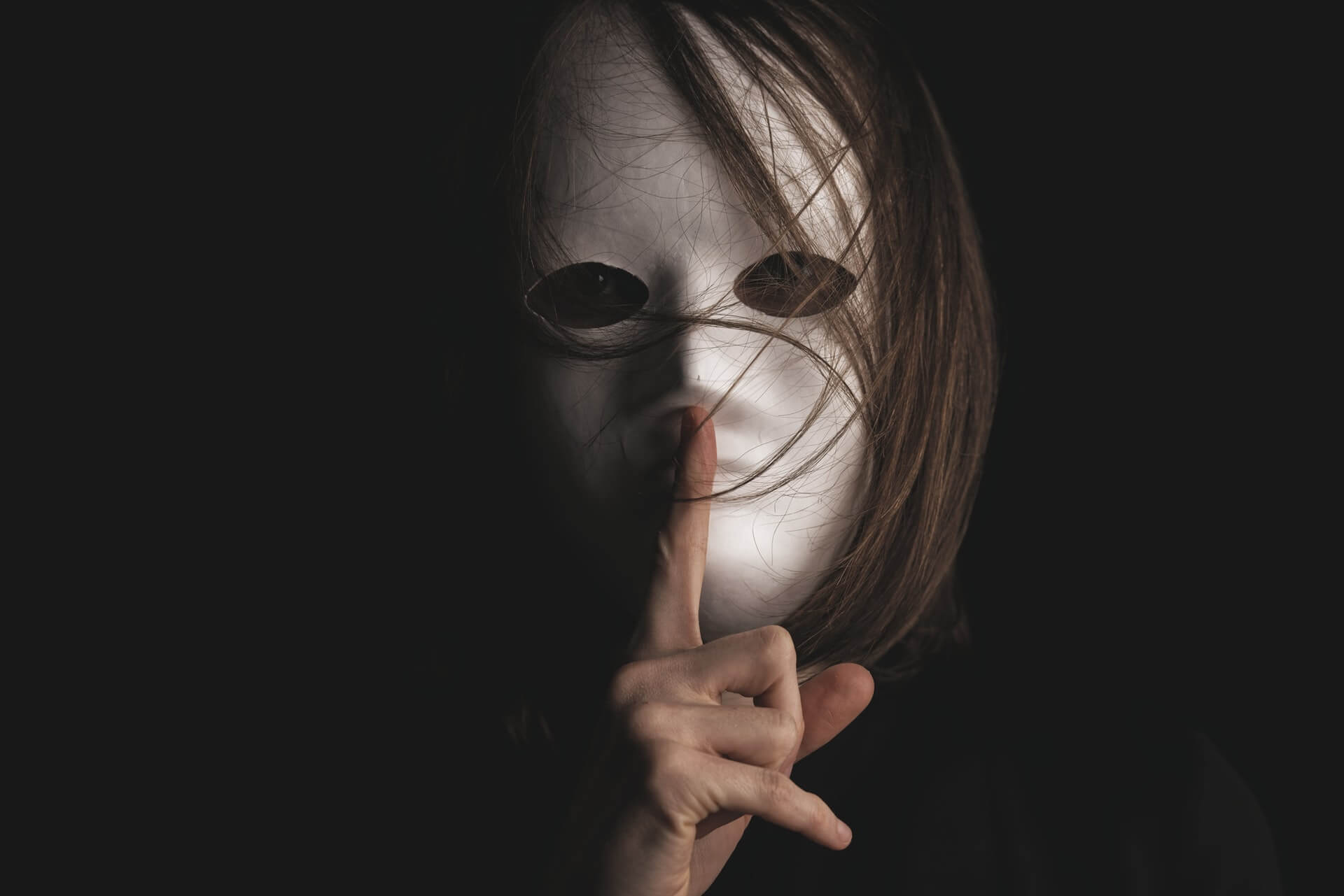 A woman wearing a mask shushing the camera representing the deceit present in travel scams