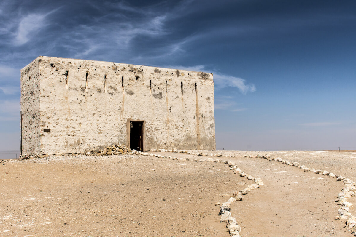 a tan ruin in front of a clear blue sky in oman