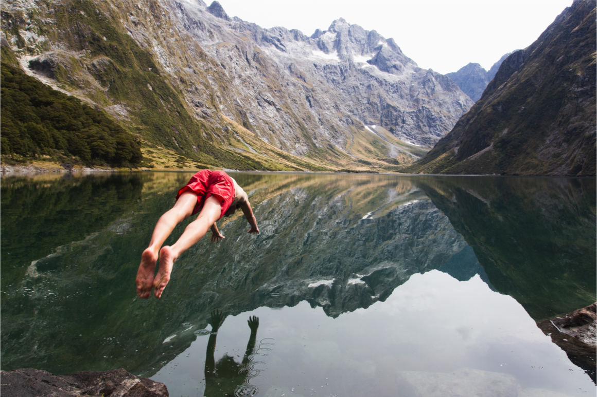 A man in red board shorts dives into cold Milford Sounds water.