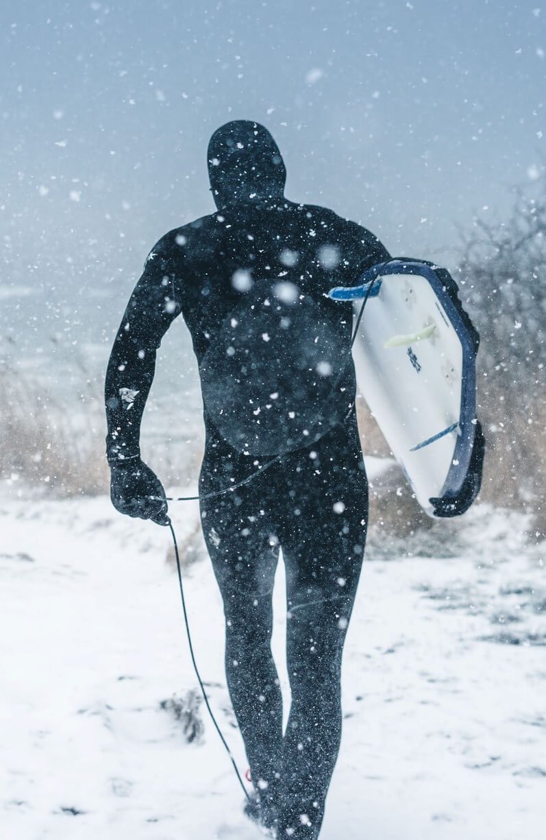 A man heading to the beach in a snowstorm wearing a thermal wetsuit
