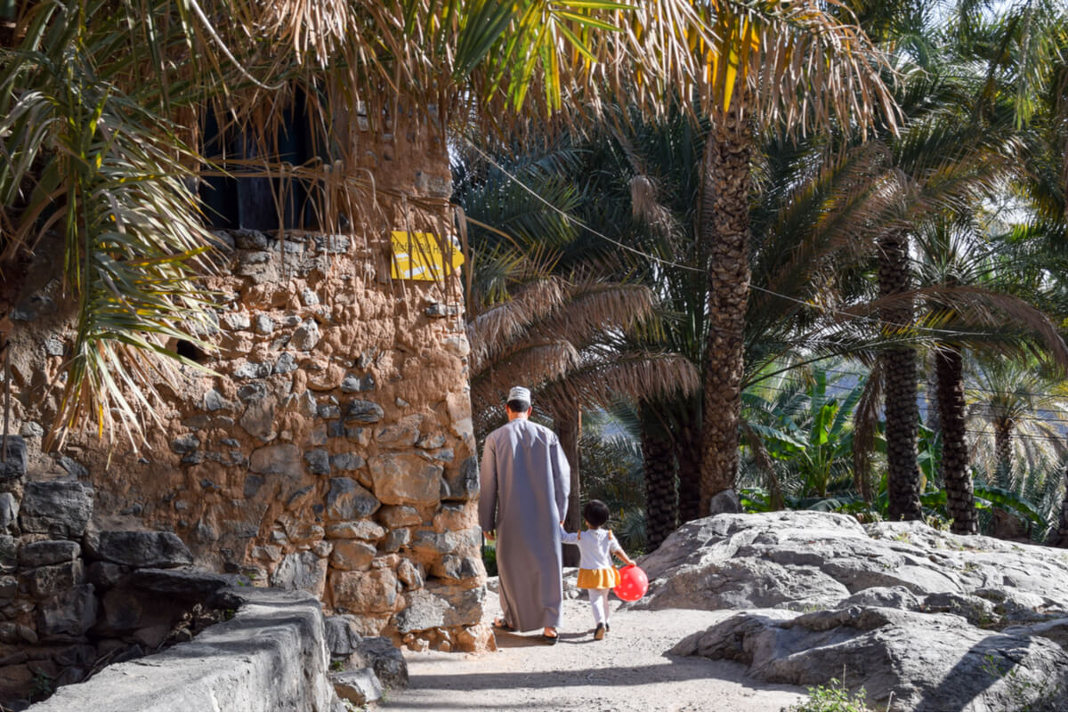 a father and child walking along a water channel in misfat al abriyyin in oman